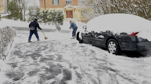 3 men shoveling snow from a driveway working around a car.